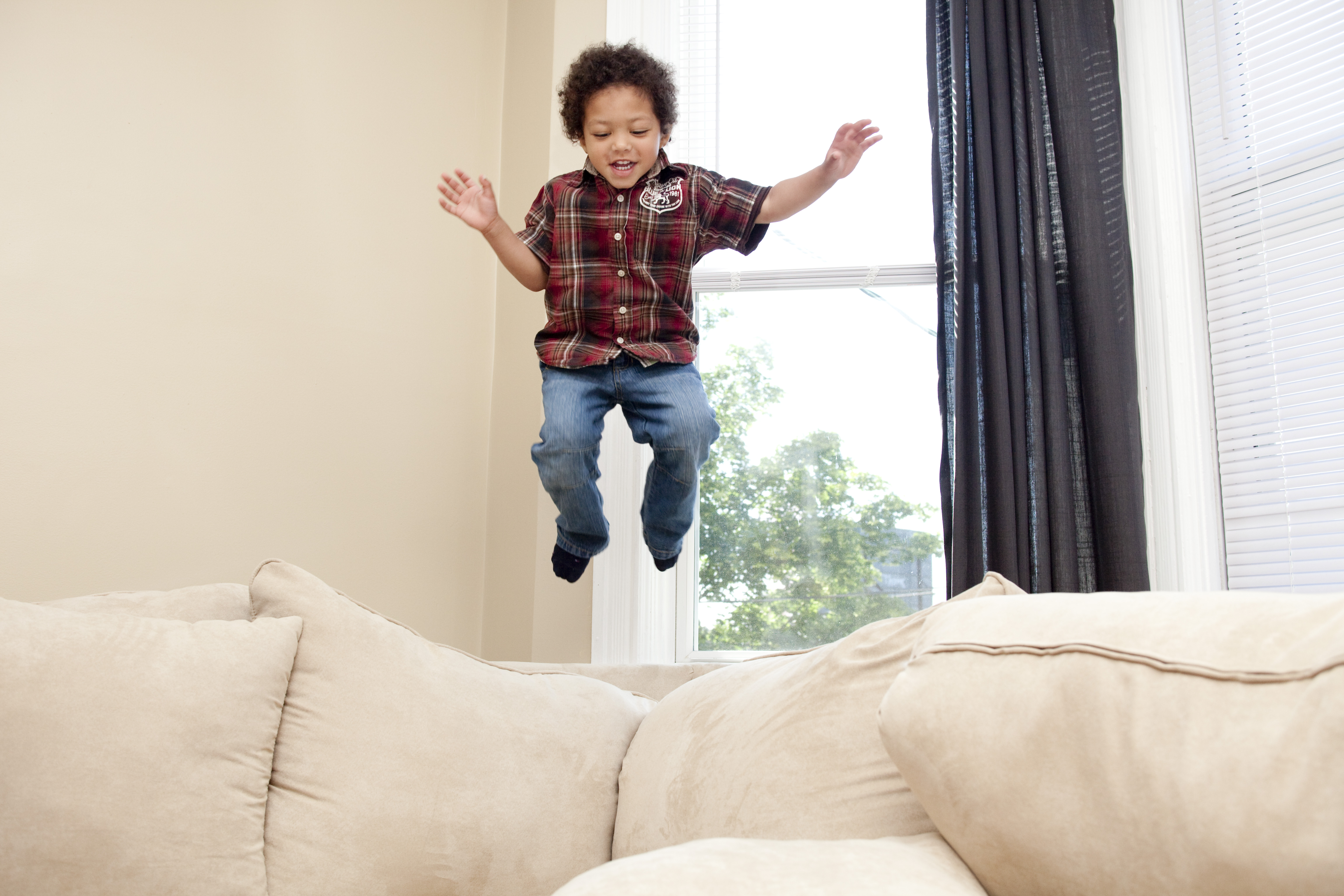 Child jumping on a couch near a window